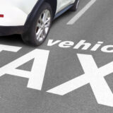 A tarmac floor with a white car parked and white text seeped into the tarmac saying vehicle tax.
