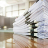 A wooden table with a stack of tax papers on top to demonstrate how long do you need to keep personal tax records in the uk.